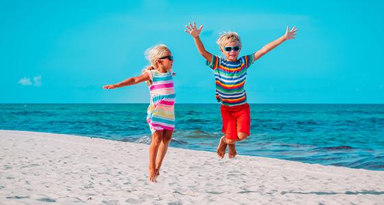 Hoppende glade barn på strand